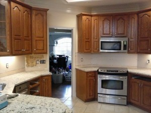 "A ""before"" shot showing the transformation from the dark cabinets to the new cool white painted kitchen cabinets."
