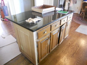A before photo of this project with painted kitchen cabinets with contrasting island.